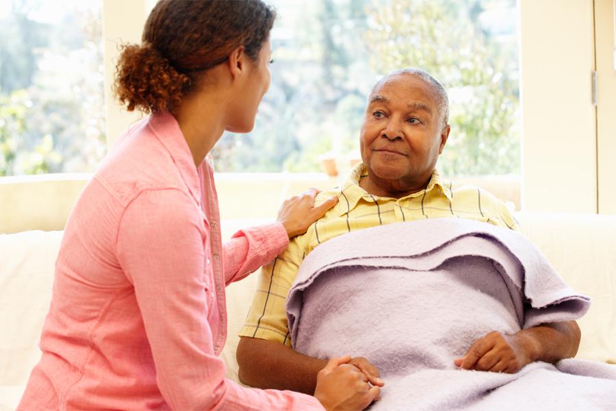 Healthcare worker tending to elderly gentleman